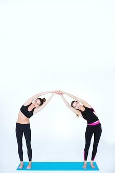 피트니스 매트에 요가 연습을하는 훈련 복을 입은 두 젊은 여성
