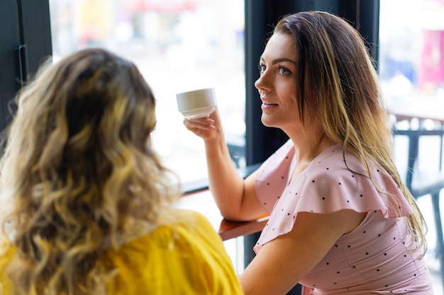 Due giovani donne che bevono caffè nella caffetteria