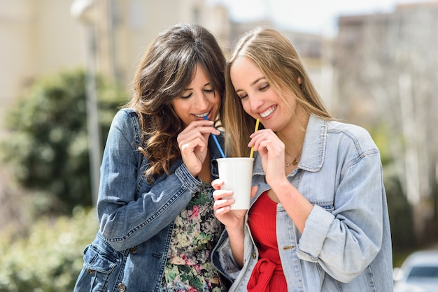 Две молодые женщины пьют то же самое, что снимают стакан вместе с двумя соломинами на открытом воздухе.