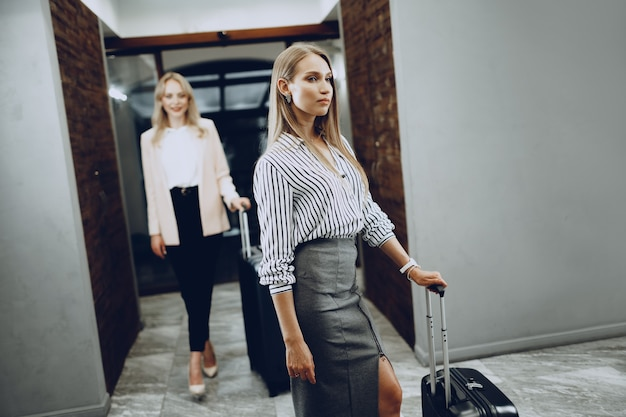 Two young women in formal clothes entering hotel lobby