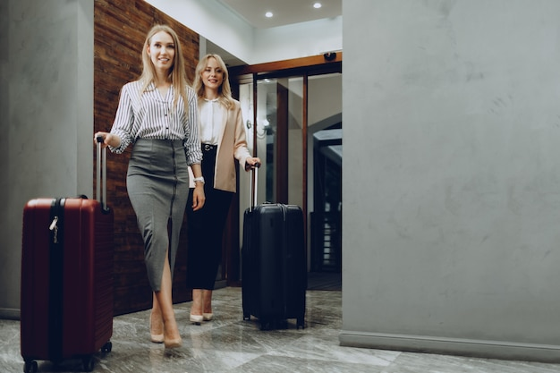 Two young women in formal clothes entering hotel lobby.