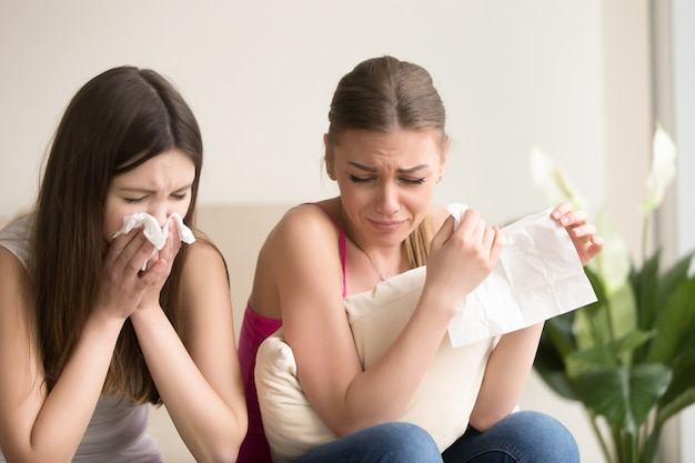 Two young women friends crying together at home