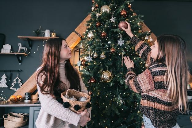 두 젊은 여자 친구가 장난감으로 크리스마스 트리를 장식합니다. 휴일 준비