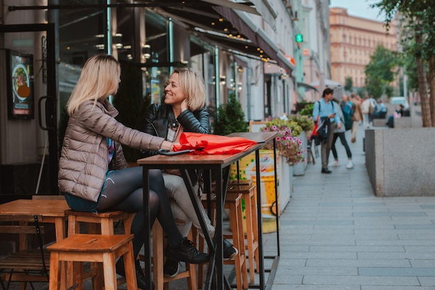 Two young women friends met in a city street cafe and have fun chatting.