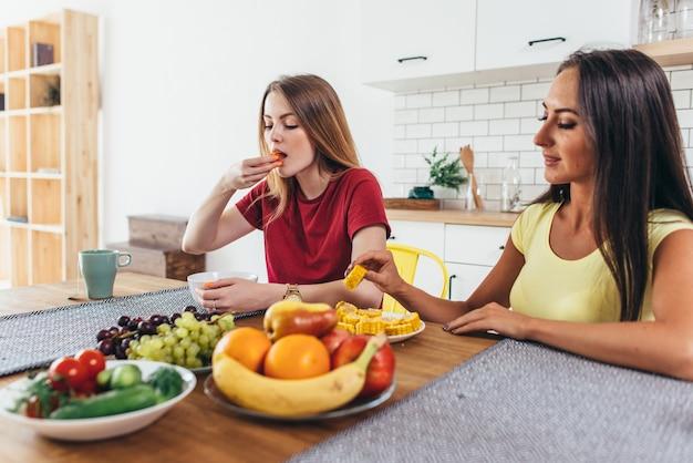 Две молодые женщины друзья сидят за столом, разговаривают и едят.