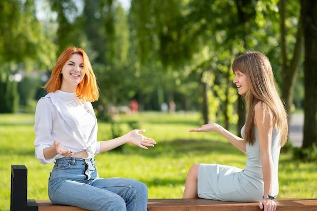 Две молодые женщины друзья сидят на скамейке в летнем парке и разговаривают, спорят.