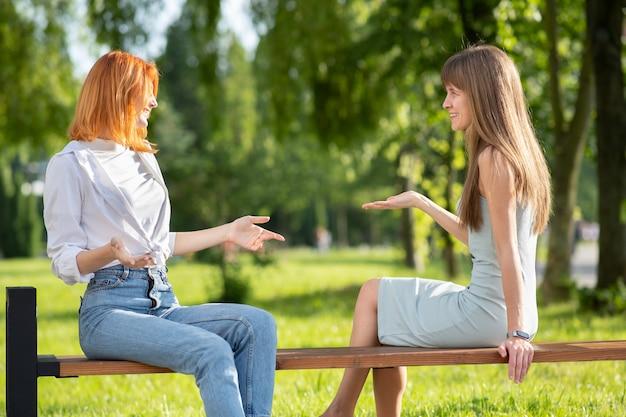 夏の公園のベンチに座って、議論を持つ2人の若い女性の友人。
