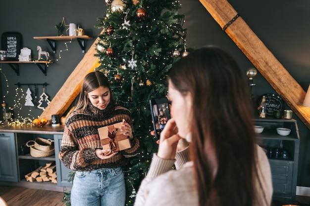 Две молодые женщины друзья фотографируются с подарками возле елки в праздники.