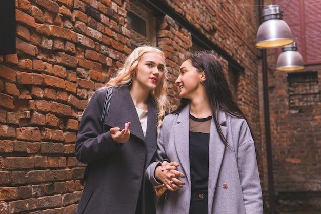 Две молодые подруги разговаривают друг с другом во дворе старого здания