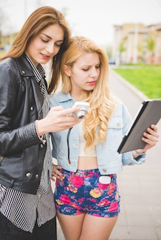 Two young women friends using devices