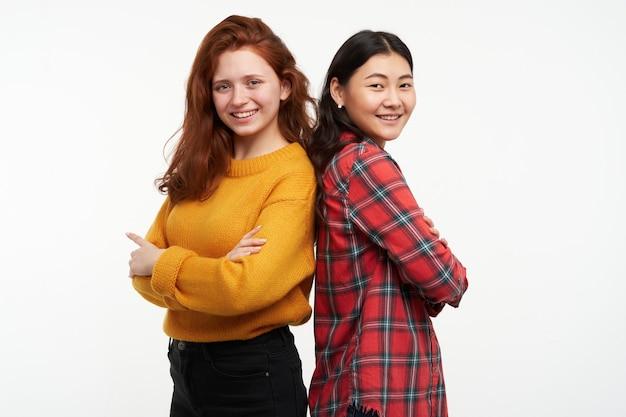 Due amiche di giovani donne. indossare maglione giallo e camicia a scacchi. in piedi schiena contro schiena con le braccia incrociate. persone e concetto di stile di vita. isolato su muro bianco