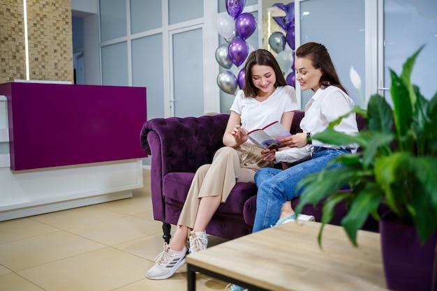 Две молодые женщины-подруги сидят на диване и разговаривают. женский дружеский чат
