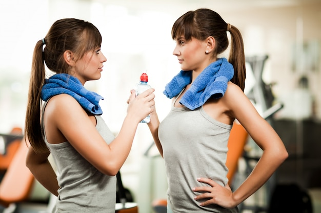 Two young women in grey sportswear with towels standing with bottle of water and looking at each other in gym