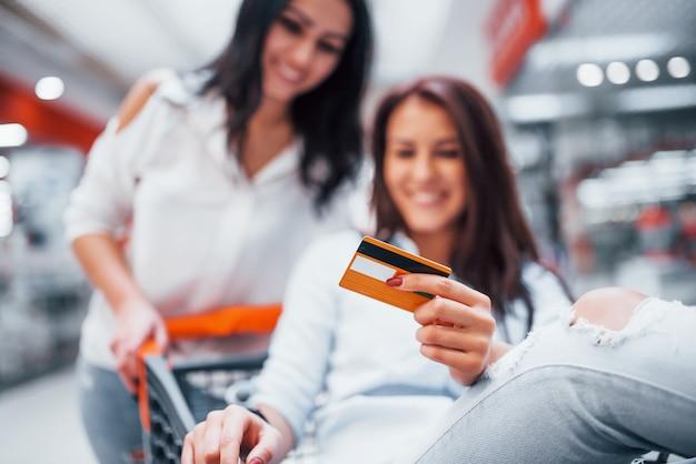 スーパーマーケットの買い物かごに乗って走ったり、乗ったりして、2人の若い女性が楽しんでいます。
