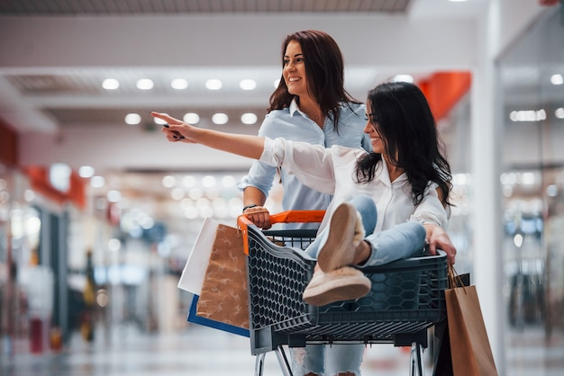 Two young women have fun by running and riding in the shopping basket in supermarket.