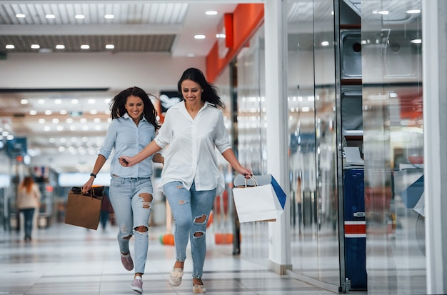 Two young women have fun and running. having shopping day together in the supermarket.