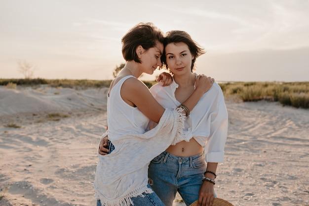 Due giovani donne che hanno divertimento sulla spiaggia al tramonto, romanticismo gay amore lesbico