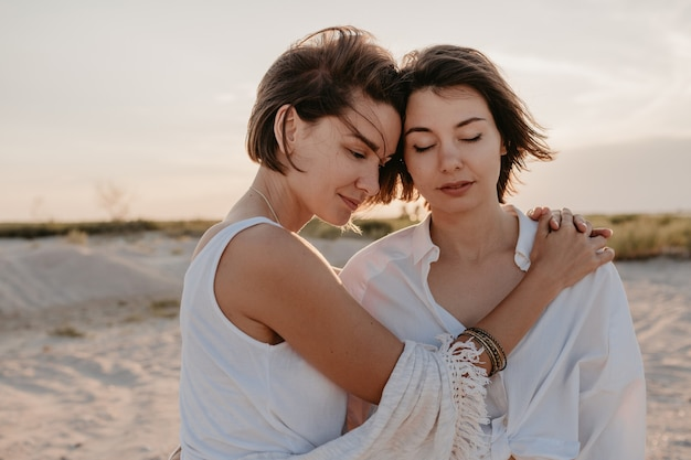 Two young women having fun on the sunset beach, gay lesbian love romance