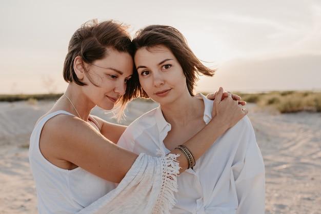 Two young women having fun on the sunset beach, gay lesbian love romance