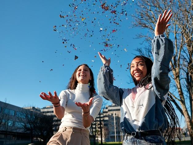 Две молодые женщины веселятся, бросая конфетти, выглядят счастливыми и носят повседневную одежду на улице