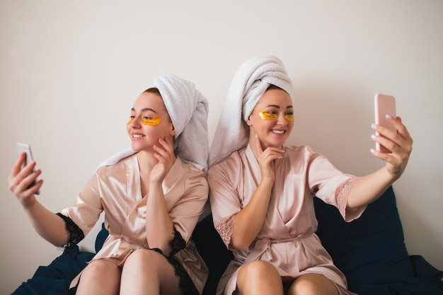 Two young women having fun with patches under their eyes