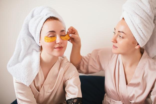 目の下でパッチを楽しんでいる2人の若い女性。タオルとパジャマを着た2人の友人が家で一緒に楽しいスパパーティーをします。