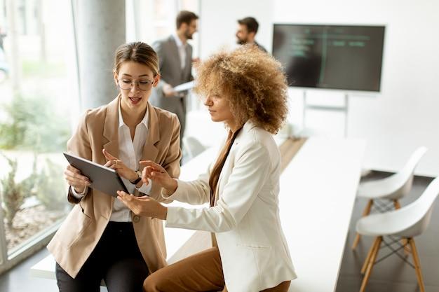 Две молодые женщины держат цифровой планшет и работают в современном офисе