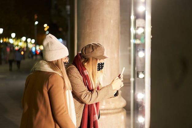 상점 창에서 찾고 겨울 옷에 밤에 도시에서 두 젊은 여성. 그들 중 한 명은 휴대 전화로 무언가를 찍습니다.