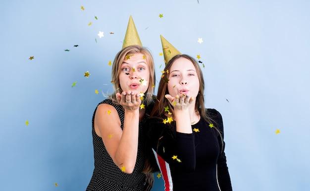 파란색 배경 위에 생일을 축하하는 풍선을 들고 생일 모자에 두 젊은 여성, 색종이 불고