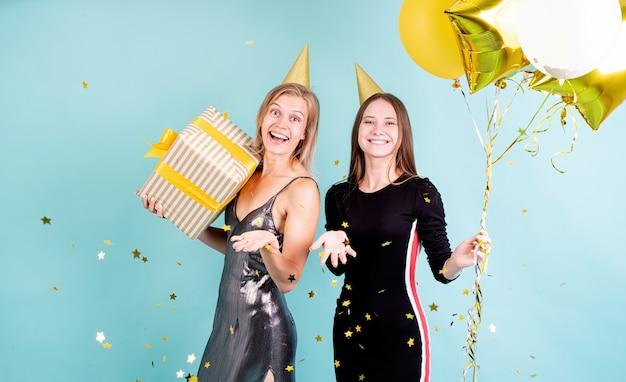 파란색 배경 위에 생일을 축하하는 풍선을 들고 생일 모자에 두 젊은 여성
