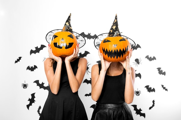 검은 드레스와 마녀 모자를 쓴 두 젊은 여성이 얼굴에 할로윈 호박을 들고 있습니다.