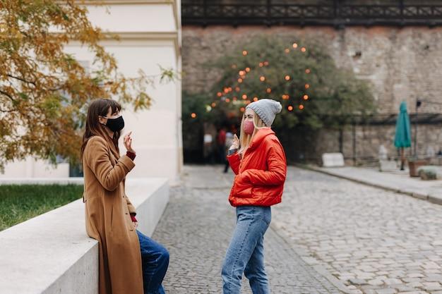 医療衛生マスクの2人の若い女性が屋外の距離で挨拶します。コロナウイルスの発生の社会的距離と予防。