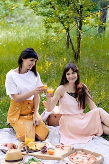 晴れた日に外の公園で2人の若い女性。ピザ、パン、オレンジジュース、チーズ、フルーツと芝生の上のピクニックの設定