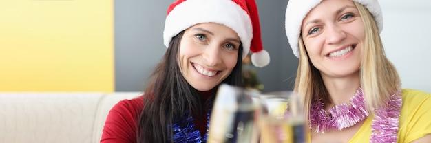샴페인을 마시는 산타 클로스 모자에 두 젊은 여성