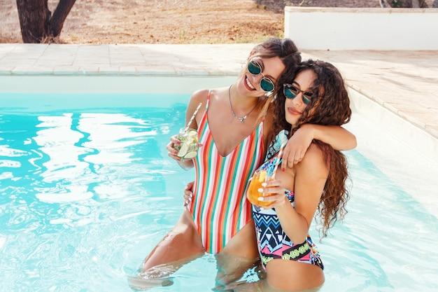 Две молодые женщины в купальниках расслабляются и пьют тропические коктейли в бассейне, вид сверху крупным планом