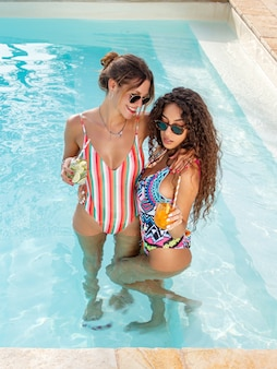 Две молодые женщины в купальниках расслабляются и пьют тропические коктейли в бассейне
