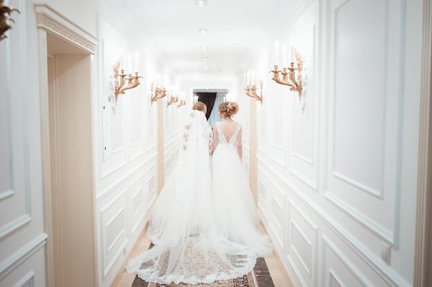 ウェディングドレスを着た2人の若い女性が長い白い廊下を歩く