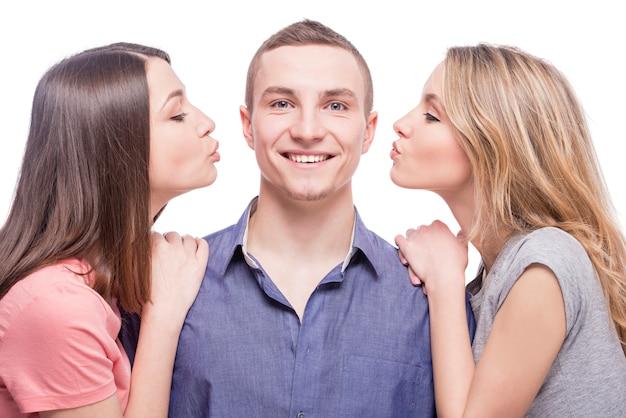 Две молодые женщины целуются с мужчиной.