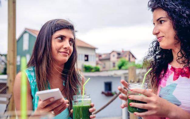緑の野菜のスムージーを屋外で保持しながらお互いを見ている2人の若い女性