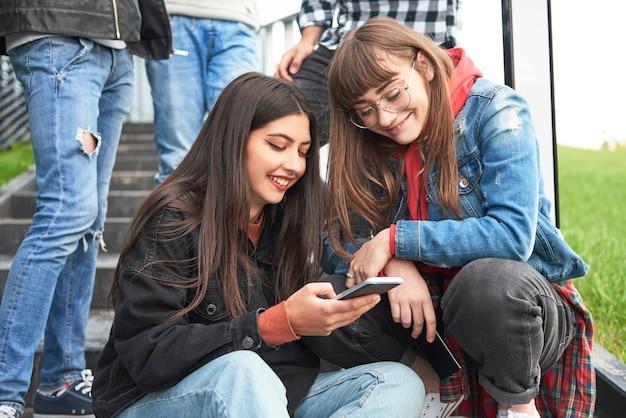 携帯電話を見ている2人の若い女性