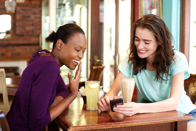 Two young women looking at mobile phone at cafe