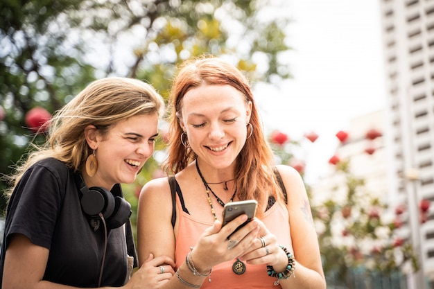 Two young women looking at the mobile phone while laughing in the street