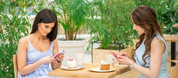 카페에 앉아있는 동안 자신의 스마트 폰을 찾고 두 젊은 여성. 기술 사람들 중독