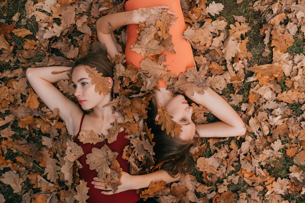 Two young women lying on ground and covered with autumn leaves  and looking at different directions.