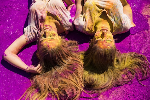 Two young women lying on purple holi color powder