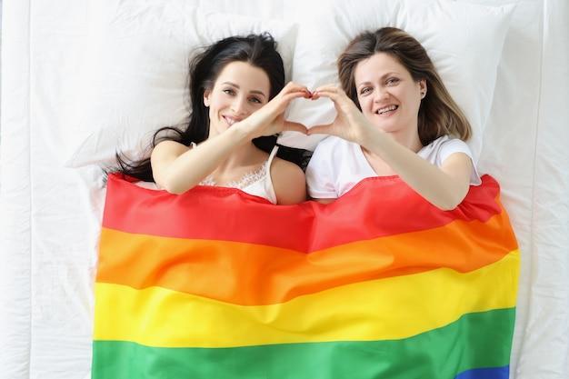Две молодые женщины, лежащие под флагом лгбт и показывающие сердце руками, концепция женской любви