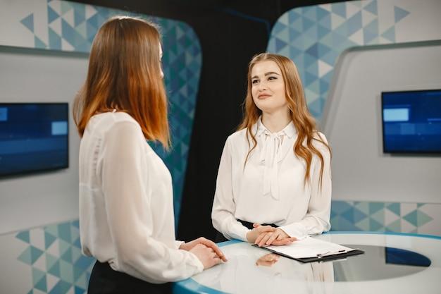 テレビのインタビューのセットにいる 2 人の若い女性、女性に焦点を当てています。テレビスタジオ。