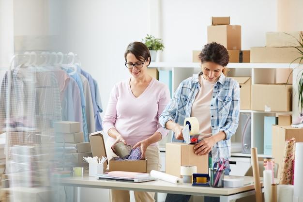 オンラインクライアント用の小包を梱包する2人の若い女性