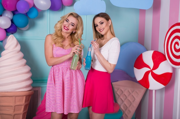 Two young women in pink dresses drink juice in a glass bottle.