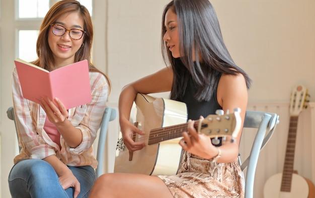 ギターを弾き、楽しく歌う2人の若い女性。